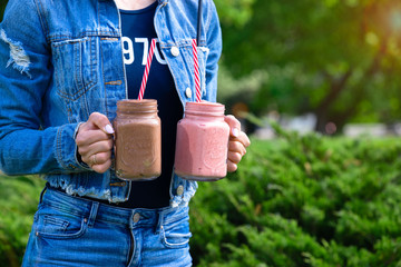 Girl in denim clothes holding two smoothie