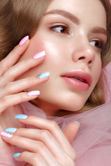 Beautiful girl with light make-up and gentle manicure in pink clothes. Beauty face. Design nails. Photo taken in studio on pink background