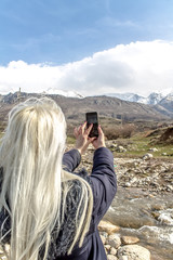 Girl takes pictures of a mountain landscape