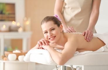 Beautiful young woman having massage with body scrub in spa salon