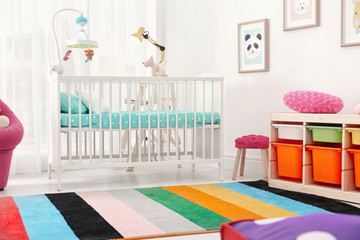 Colorful baby room interior with comfortable crib