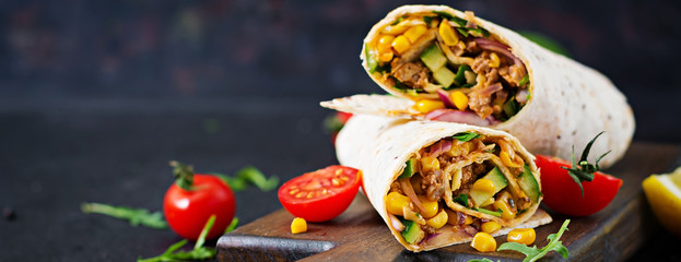 Burritos wraps with beef and vegetables on  black background. Beef burrito, mexican food. Wall mural