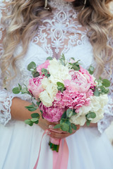 the bride in a chic white dress is holding a wedding bouquet of beautiful roses