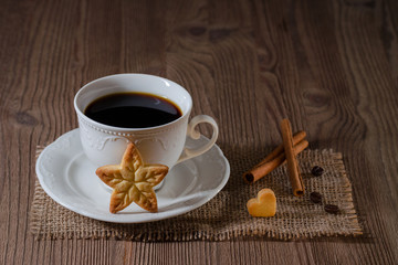 a cup of coffee and cookies like star and heart with cinnamon, coffee beans on wooden table