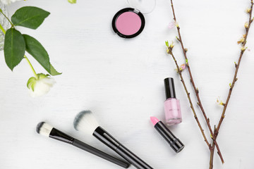 Pink themed spring cosmetics or makeup flat lay still life with fresh flowers and buds, soft bristle brushes, lipstick, nail varnish and blusher on white