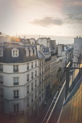 Rooftop view of historical buildings in Paris, France overlooking a narrow street from a top floor balcony on a cloudy day in November