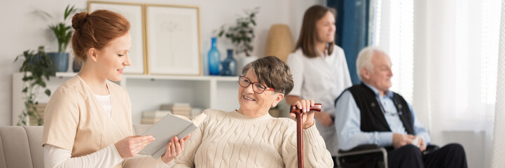 Nurse reading to elderly woman