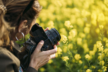 crop woman taking picture in field