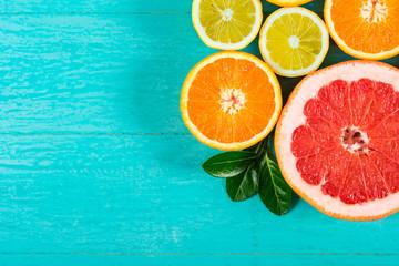 Sliced grapefruit, oranges and lemon. Citrus fruits collection on blue wooden background Fototapete