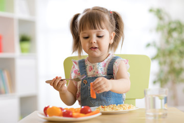 Cute child little girl eating healthy vegetables at home