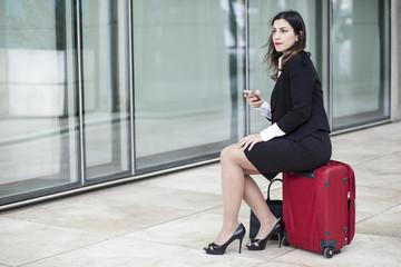 90b7ed01697e Manager vestita con un tailleur nero con il cellulare in mano è seduta  sopra una valigia