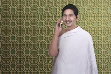 Handsome asian pilgrim man talking on the mobile phone