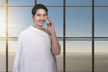 Young asian muslim man with ihram cloth using cellphone