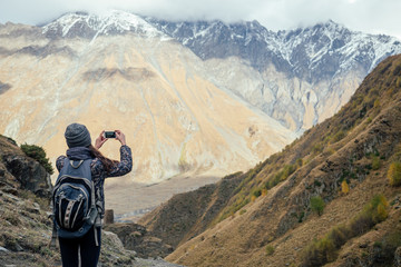 beautiful girl takes pictures of mountains in Georgia
