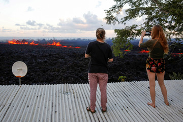 Jolon Clinton, 15, (L), and her sister, Halcy, 17, take photos of a fissure near their home on the outskirts of Pahoa