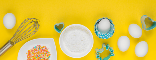 Eggs, flour, sugar and ingredients for baking on a yellow background flat fork on top of a long banner
