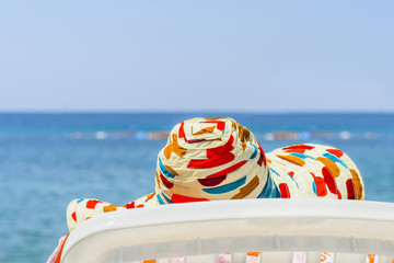 Woman on the beach in colorful hat against sea and blue sky.