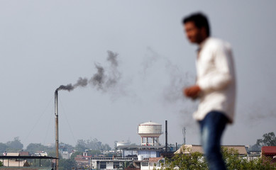 A man stands on a hill as smoke emits from a chimney of a leather tannery at an industrial area in Kanpur