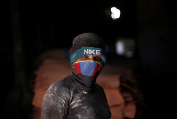 A worker wearing a mask pauses as he works inside a leather tannery at an industrial area in Kanpur