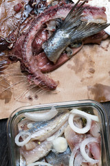 raw fresh herring and giblets in the paper bag, preparation to salt fish