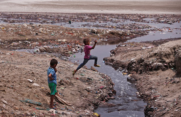 A boy jumps over a drain flowing with waste water from the leather tanneries into the river Ganges in Kanpur