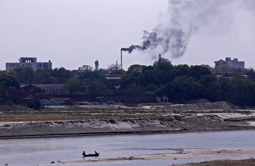 Men row a boat in the river Ganges as smoke emits from a chimney of a leather tannery at an industrial area in Kanpur