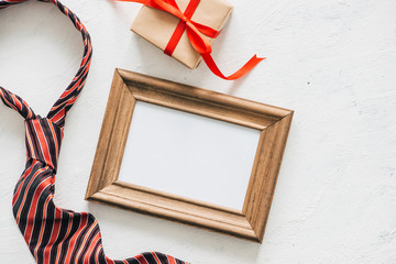 Flatlay image of gift box, necktie and blank frame. Father's day concept