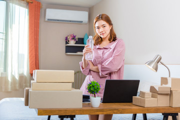 Young asian online seller businesswoman working at home taking a break from working on her online orders to drink water and thinking about her business
