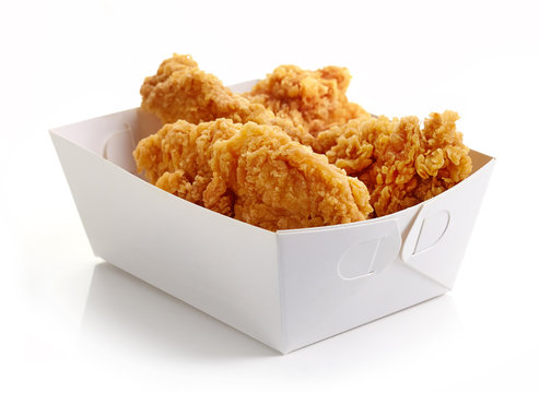 Fried breaded chicken fillet in white cardboard box isolated