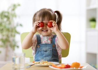 Happy child girl having fun with food vegetables at kitchen holds tomatoes before her eyes like in glasses