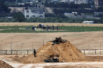 Israeli soldiers are seen in position on the Israeli side of the border fence between Israel and the Gaza Strip
