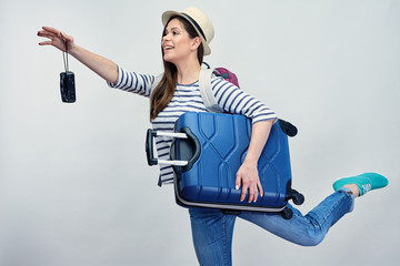 Woman tourist going on trip with camera and suitcase.