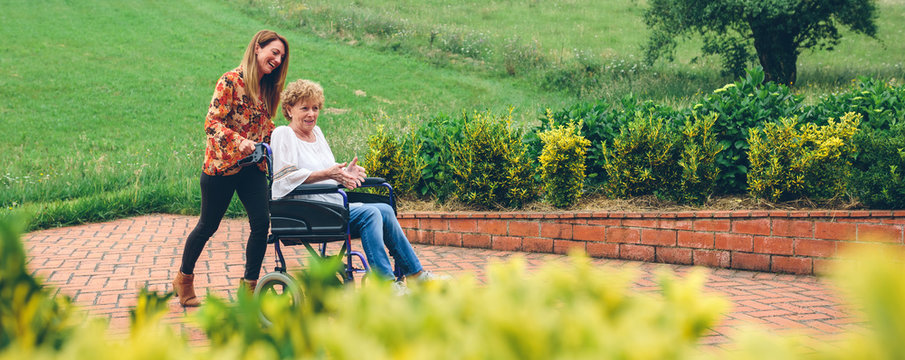 Young woman carrying her mother in a wheelchair through the garden