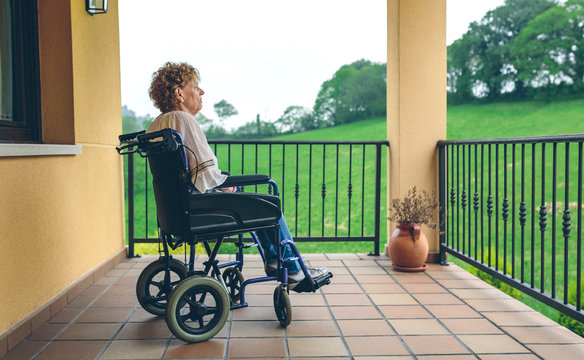 Serious older woman in a wheelchair in the porch