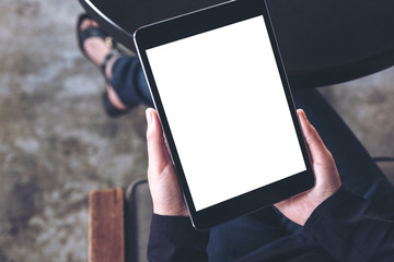 Top view mockup image of a woman sitting cross legged and holding black tablet pc with blank white desktop screen