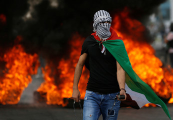 Palestinian demonstrator stands in front of burning tires during a protest marking the 70th anniversary of Nakba, near the Jewish settlement of Beit El, near Ramallah, in the occupied West Bank