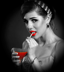 Pin up girl drink bloody Mary cocktail. Pin-up retro female style. Girl wearing dress seduces men. Cocktail with new taste. Black white photo with red lips color accent. She bites straw from cocktail.