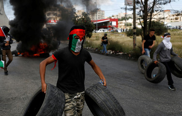 Palestinian demonstrator carries tires to be burnt during a protest marking the 70th anniversary of Nakba, near the Jewish settlement of Beit El, near Ramallah, in the occupied West Bank