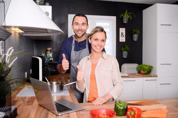 happy and cheerful young couple cooking organic vegetables together at home