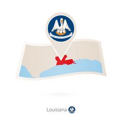 Folded paper map of Louisiana U.S. State with flag pin of Louisiana.
