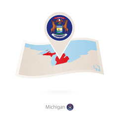 Folded paper map of Michigan U.S. State with flag pin of Michigan.