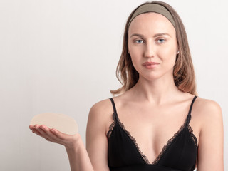 Young blonde woman holds in her hand silicone breast implant, before surgery.