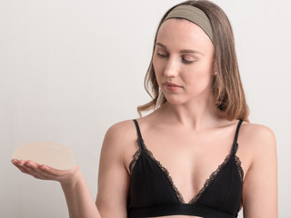 Young woman looking at her breast implant before surgery.