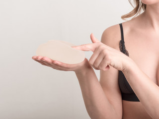 Young woman touch her breast implant before surgery.