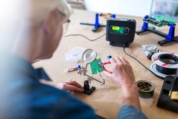 Senior woman in electronics workshop