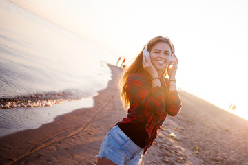Happy attractive red-haired girl is enjoying favorite music on walk. Beautiful young woman in shirt uses headphones