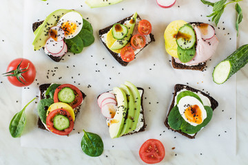 Different sandwiches with vegetables, eggs, avocado, tomato, rye bread on light marble table. Top vew. Appetizer for party. Flat lay.