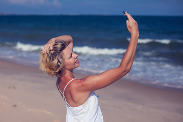 Smiling young woman take a selfie photo at sandy beach by the sea at sunset