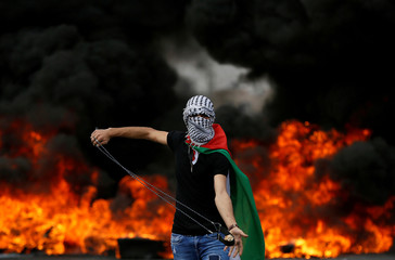 Palestinian demonstrator holds a sling during a protest marking the 70th anniversary of Nakba, near the Jewish settlement of Beit El, near Ramallah, in the occupied West Bank