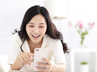 happy woman sitting on couch and watching smart  phone